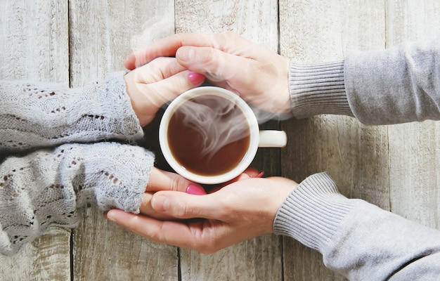 Une tasse de thé dans les mains d'un homme et d'une femme. mise au point sélective. Photo Premium