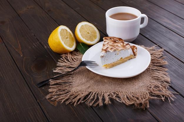 Tasse de thé avec du lait et un morceau de citron pue servi sur une table en bois foncé Photo gratuit