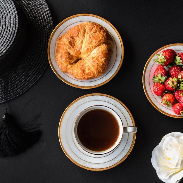 Tasse de thé avec du pain et des fraises sur fond noir Photo gratuit