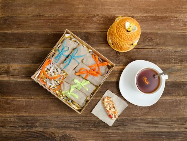 Tasse à thé, emballage de barres et sucrier. table en bois Photo Premium