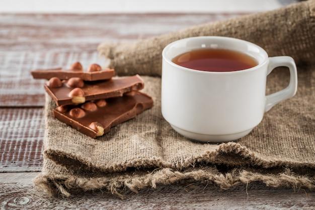Une tasse de thé est un chocolat noir sur le bois Photo Premium