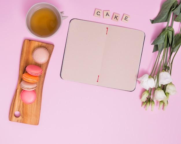 Tasse de thé de fines herbes; blocs de gâteau de texte; macarons; journal vierge et eustoma blanc sur fond rose Photo gratuit