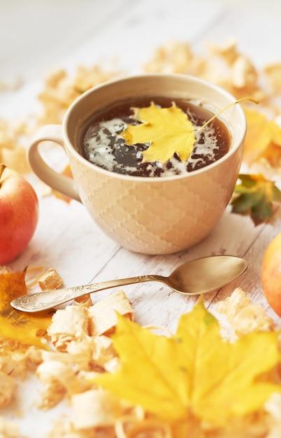 Tasse à thé sur un fond d'automne avec des pommes, des feuilles et des fleurs. Photo Premium