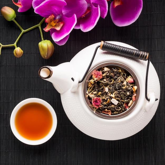 Tasse de thé et herbes séchées à la fleur d'orchidée sur un napperon noir Photo gratuit