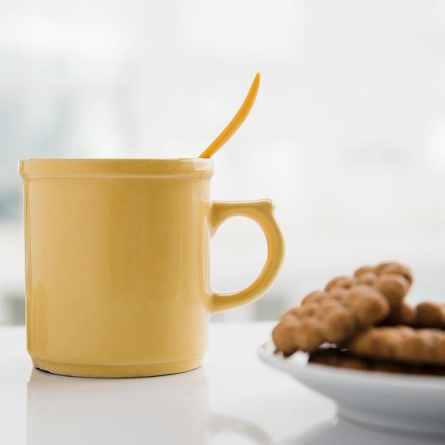 Tasse de thé jaune avec des biscuits Photo gratuit