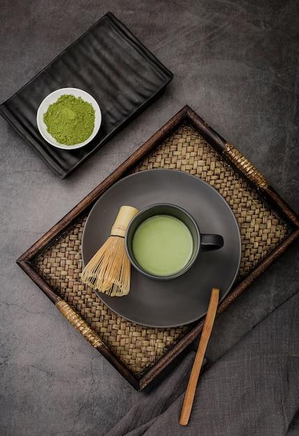 Tasse de thé matcha sur plateau avec fouet en bambou Photo gratuit