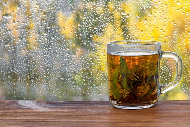 Une tasse de thé à la menthe avant la fenêtre goutte de pluie automne. Photo Premium