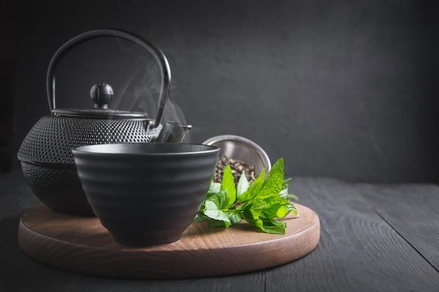 Tasse de thé à la menthe et bouilloire sur noir Photo Premium