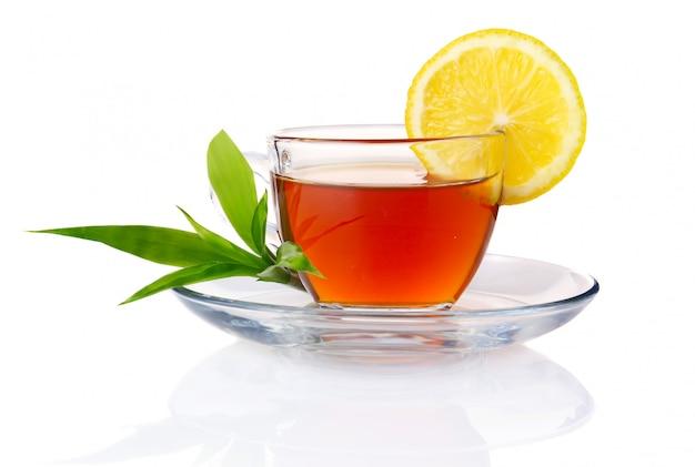 Tasse de thé noir au citron et feuilles vertes isolées Photo Premium