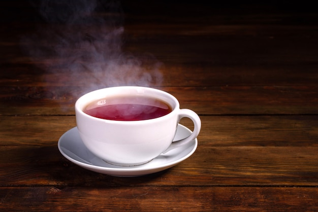 Une Tasse De Thé Noir Fraîchement Moulu, Une Vapeur Qui S'échappe, Une Douce Lumière Chaude Photo Premium