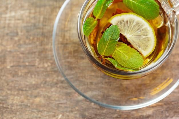 Tasse de thé noir à la menthe laisse sur une table en bois Photo Premium