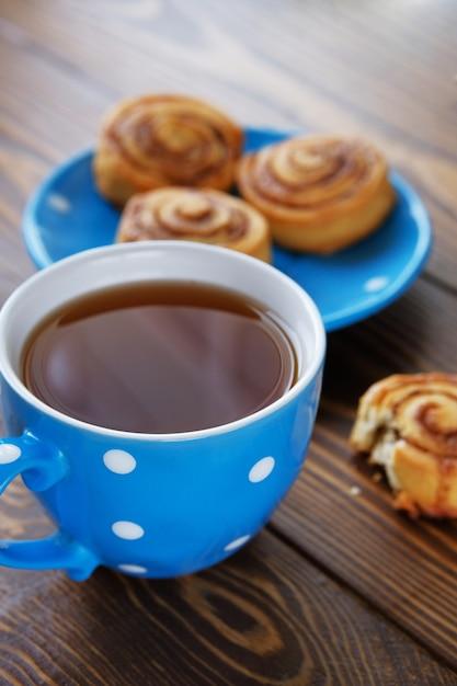 Une tasse de thé noir et un petit pain mordu sur une table en bois Photo Premium