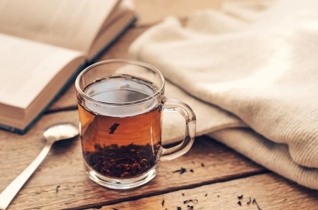 Une tasse de thé noir sur une table en bois avec un livre et un pull chaud Photo Premium