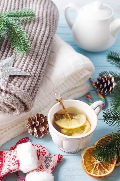 Une tasse de thé pour la nouvelle année. un plaid confortable, une écharpe tricotée et du thé chaud sur un fond en bois bleu Photo Premium