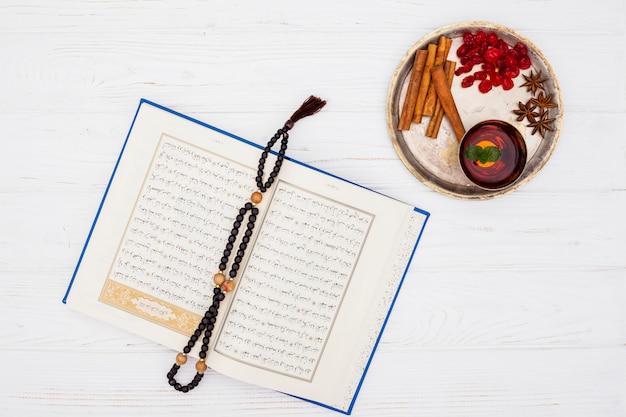 Tasse de thé près des épices sur un plateau et livre avec des perles Photo gratuit