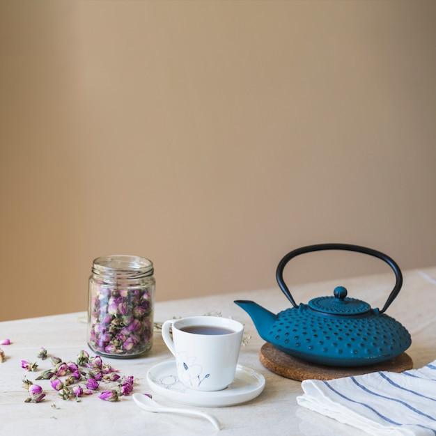 Tasse de thé avec théière et éléments de petit déjeuner Photo gratuit