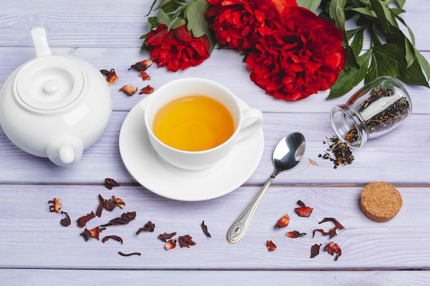 Tasse de thé vert sur la table avec des fleurs de pivoine fraîche Photo Premium