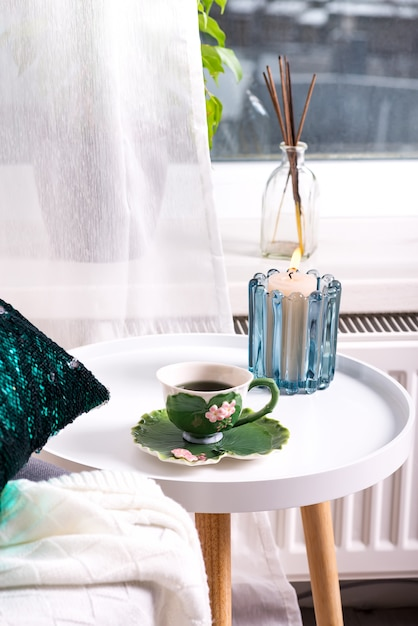 Une Tasse De Tisane Sur Une Table, Une Couverture De Laine Tricotée Sur Une Chaise Et Une Bougie Sur La Fenêtre. Intérieur De La Chambre Photo Premium