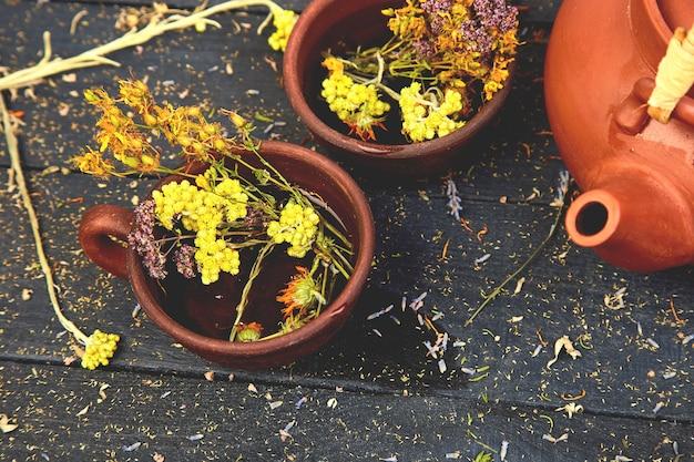 Tasse de tisane - tutsan, sagebrush, origan, helichrysum, lavande près de la théière brune sur du bois foncé. thé aux herbes. herbes sèches et fleurs, phytothérapie. Photo Premium