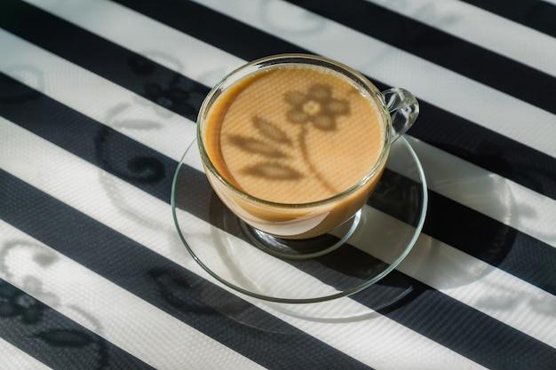 Tasse Transparente De Café Crémeux Sur Fond Sombre. La Lumière Du Soleil Et Les Ombres Dures. Image Tonique Avec Espace De Copie Photo Premium