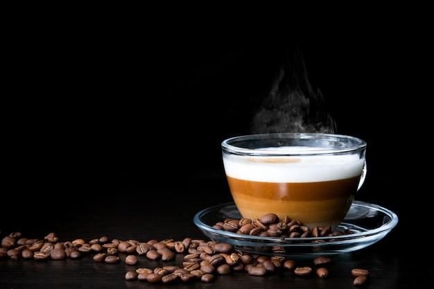 Tasse en verre de cappuccino chaud avec des couches de café Photo Premium