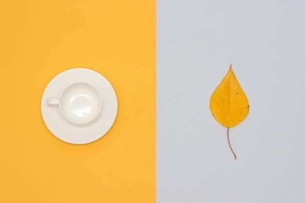 Tasse vide blanche avec soucoupe et feuille d'automne Photo Premium