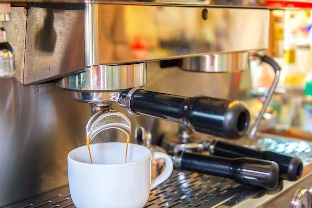 Tasses blanches se tenant sur la grille de la machine à café et du café coulant dedans Photo Premium
