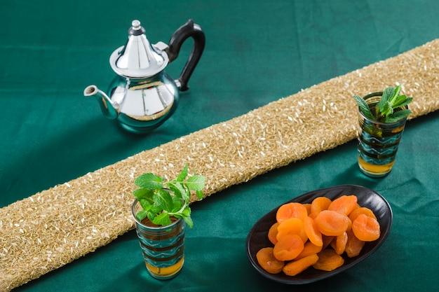 Tasses de boisson près de la théière et des abricots secs Photo gratuit