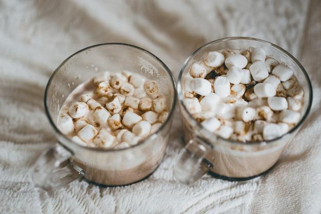 Tasses de cacao avec des guimauves près de la cheminée. Photo gratuit