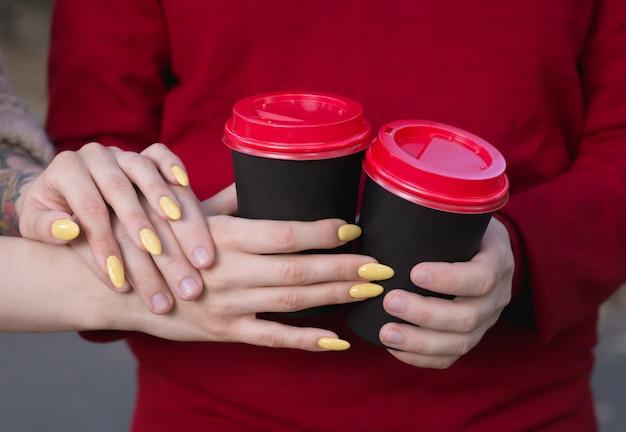 Tasses à café dans les mains des jeunes Photo Premium