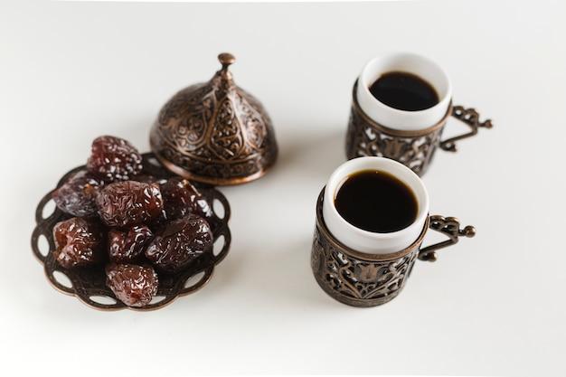 Tasses à Café Avec Des Dates Sur La Soucoupe Photo gratuit