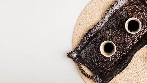 Tasses de café sur le plateau contre le tapis Photo gratuit