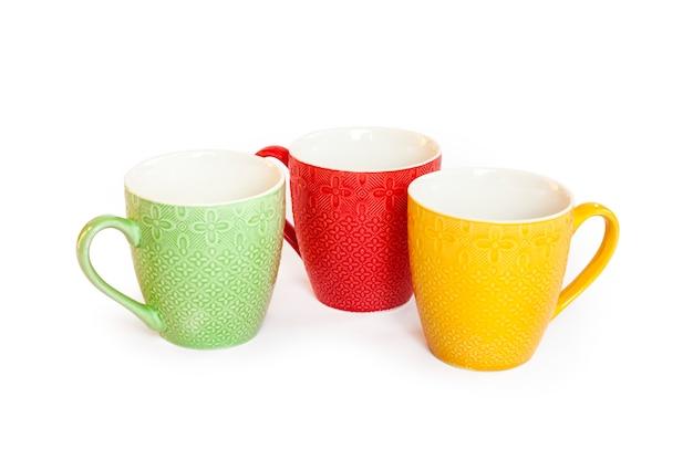 Tasses Colorées Isolés Sur Une Surface Blanche Photo Premium