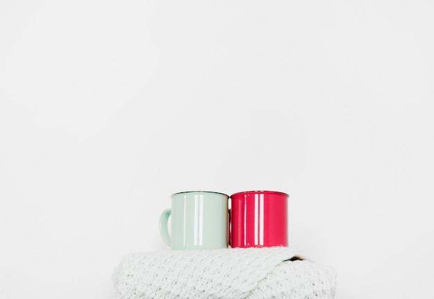 Tasses debout sur une écharpe chaude Photo gratuit