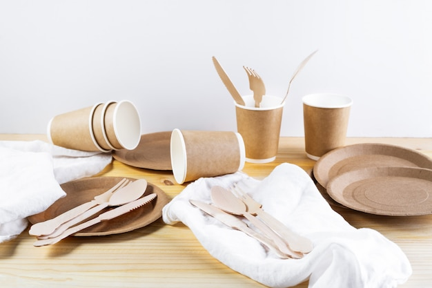 Tasses en papier marron, assiettes, couverts en bois, serviettes en lin sur fond en bois Photo Premium