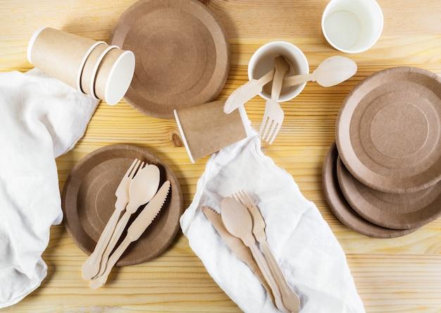 Tasses en papier marron, assiettes, couverts en bois, serviettes en lin sur fond en bois Photo Premium