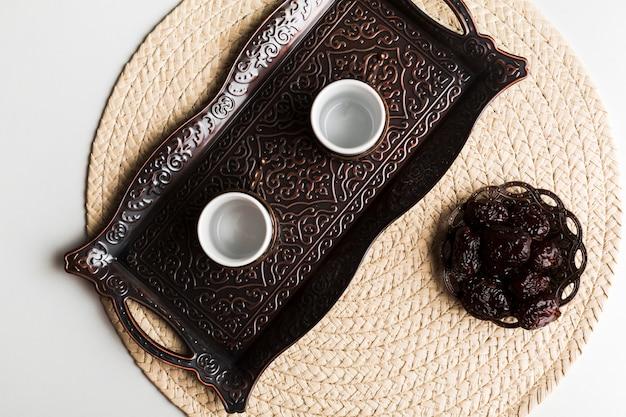 Tasses sur le plateau près de la soucoupe avec des pruneaux au tapis Photo gratuit