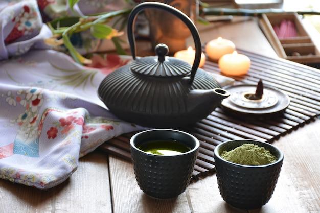 Tasses remplies de thé japonais, d'eau chaude, d'encens et de bougies Photo Premium