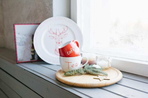 Tasses Rouges Et Blanches Pour Le Thé Et Le Café Sur Un Rebord De Fenêtre Dans Un Décor D'intérieur Photo Premium