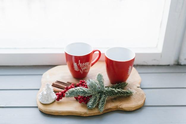 Tasses Rouges Avec Du Thé, Du Café Ou Du Vin Chaud Sur Le Rebord De La Fenêtre Dans Le Décor D'une Maison Photo Premium