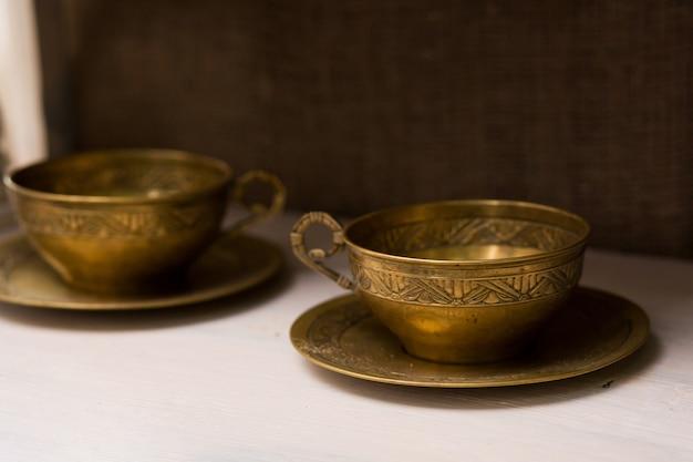 Tasses à Thé Antiques Avec Soucoupes En Cuivre. Articles De Décoration Inhabituels Photo Premium