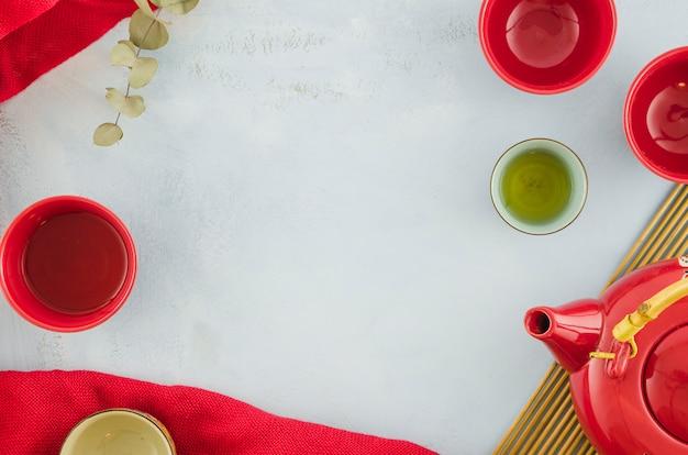 Tasses à thé rouges vides et théière sur fond blanc Photo gratuit