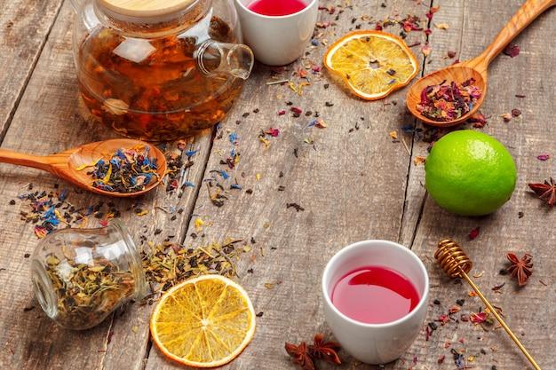 Tasses de tisane en bonne santé avec des fleurs de cannelle, de rose séchée et de camomille en cuillères sur fond en bois, vue de dessus Photo Premium