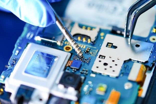 Technicien asiatique réparant un smartphone. Photo Premium