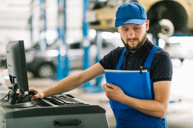 Technicien avec dossier et ordinateur au garage Photo gratuit