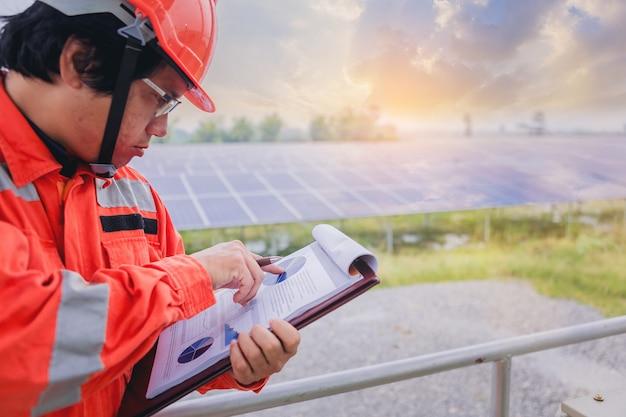 Technicien en électricité et en instrumentation prenant note du tableau statistique statistique système électrique au champ de panneaux solaires Photo Premium