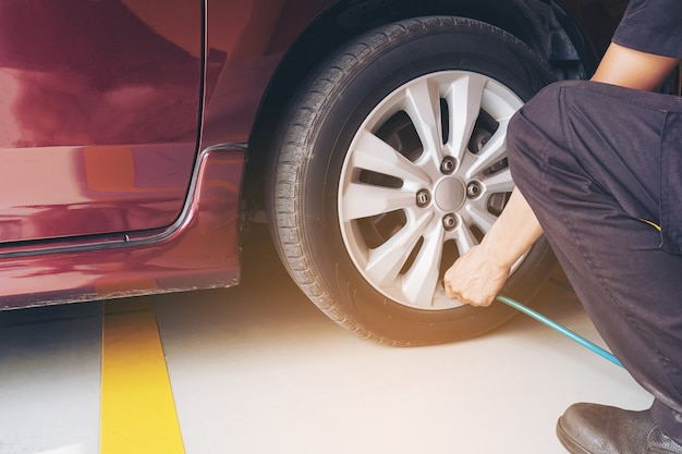 Technicien est gonfler pneu de voiture - concept de sécurité de transport de service de maintenance automobile Photo gratuit