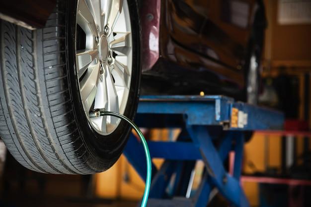 Le technicien est gonfler pneu de voiture, sécurité de transport de service de maintenance automobile Photo gratuit