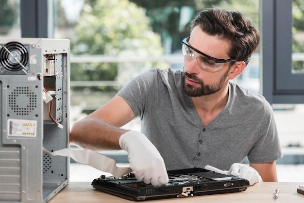 Un technicien examine un ordinateur portable cassé dans un atelier Photo gratuit