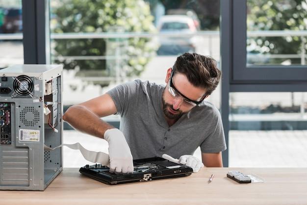 Technicien mâle fixant l'ordinateur en atelier Photo gratuit